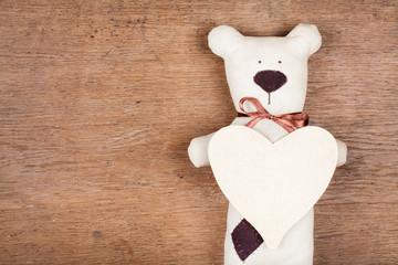 Valentine heart with handmade bear on wood background