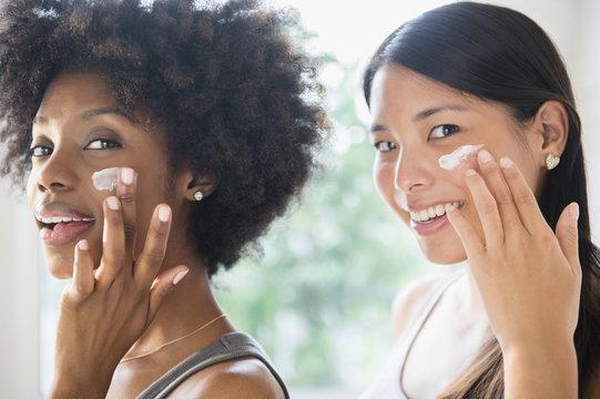 Smiling women applying moisturizer to cheeks