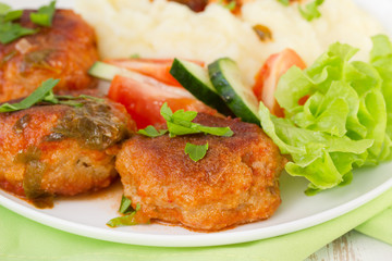 fried meatballs with mashed potato, sauce and salad