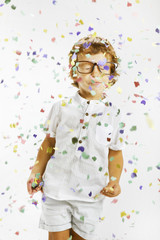 Smiling child with rimmed glasses and confetti