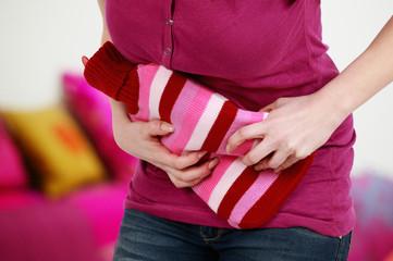 Frau hält Wärmflasche bei Bauchschmerzen