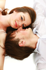 Closeup of happy young couple lying on floor. Top view