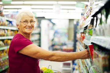 Happy senior woman at supermarket