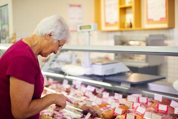 Senior woman in butchers shop..