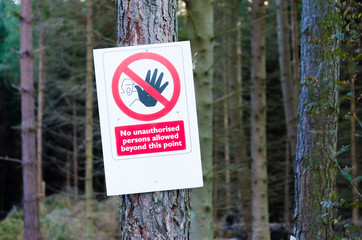 Warning sign nailed to tree in forest
