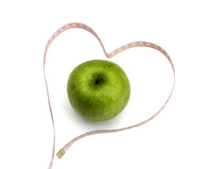 Measuring tape looking as heart and green apple