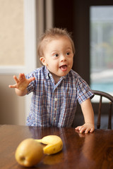 Down Syndrome child reaching for fruit on table