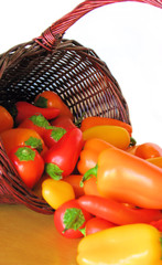 Basket Full of Colorful Peppers Spilling Out onto a Table