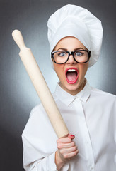 Mad chef woman cook with a rolling pin isolated on gray