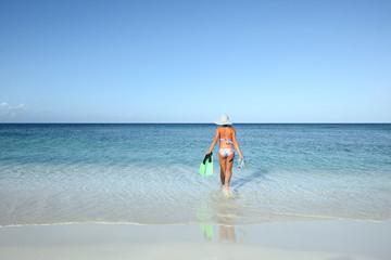 Slender woman in a bikini goes to swim