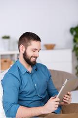 lächelnder mann schaut auf tablet-pc