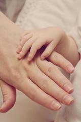 Детская рука лежит на взрослой руке