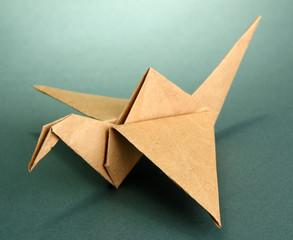 Origami crane on grey background