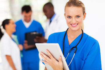 pretty medical nurse with tablet computer in hospital
