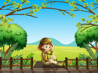 A girl sitting at the wooden bridge