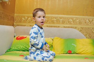 boy in blue pajamas sitting on a bed and shows the language