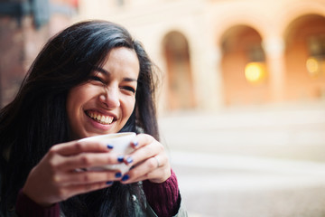 Young woman drinking coffee in a cafe outdoors.