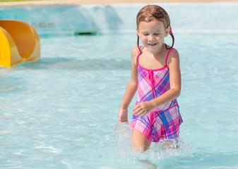 happy little girl splashing around in the pool