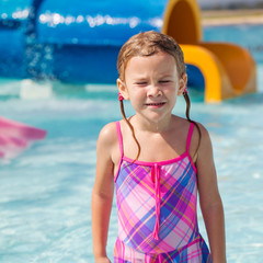happy little girl splashing around in the pool