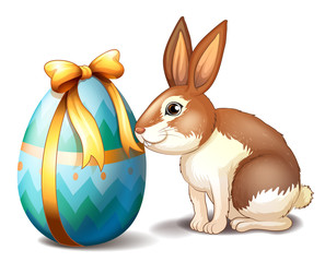 A rabbit and an Easter egg with a ribbon