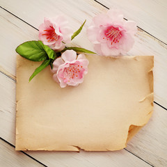 wooden background with paper frame and flowers