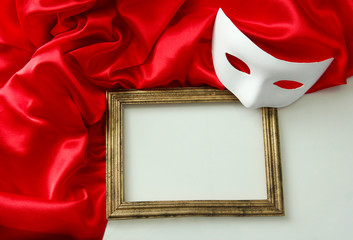 White mask, empty frame and red silk fabric, isolated on white