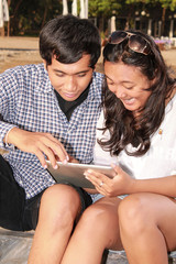 couple playing tablet at beach