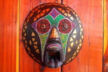 Tribal african mask on a bright cedar wood wall