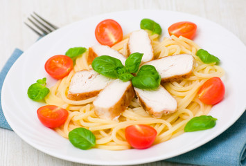 chicken breast with pasta, garnished with tomato and fresh basil
