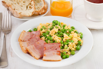 scrambled eggs, peas and bacon with bread and juice