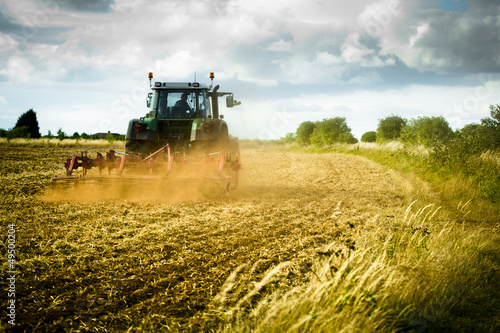 Wall mural Tractor ploughs field