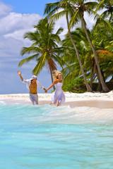 Loving couple runs on a tropical beach