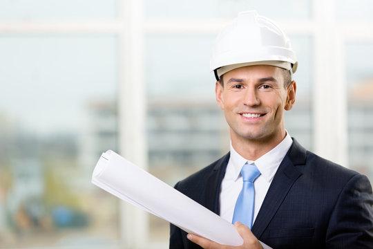 Engineer in white hard hat hands blueprint