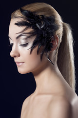 girl with feathered accessory, she looks down