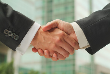 handshake with business buildings as background