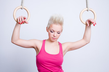 young woman on rings, pink top, look down