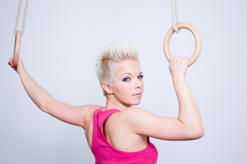 young woman on rings, pink top, back