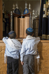 two boys standing in front of holy jewish scripts in a synagogue