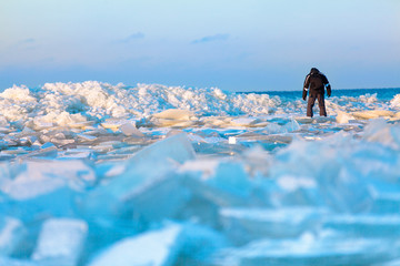Man walking on icy beach along the Baltic sea