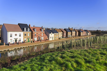 Brand new luxury houses by a canal with trees planted