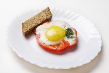 Fried egg on sweet pepper and piece of bread