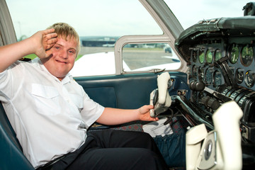 Young handicapped pilot saluting in cabin.