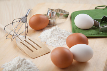 eggs, flour, cookie mold and whisk on wooden board