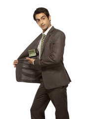 Businessman showing dollar note in pocket