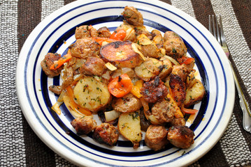 Fried Sausage and Potatoes Served on a White Plate