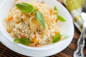 risotto with pumpkin and crispy onions in a white bowl