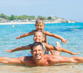 Father with his kids have fun and swim sea