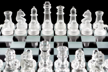 Glass chess pieces over black