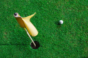 A golf ball and a hole with yellow flag