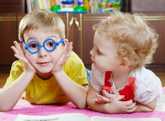 Funny brother in toy glasses with sister on floor